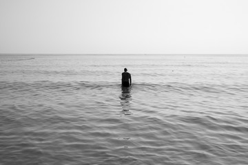 black and white picture Man walks into the sea with sadness.