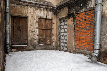 An abandoned building with boarded-up windows and doors in winter