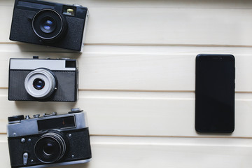Old photo cameras and black smartphone on wooden texture. Vintage film camera with on beige background. Retro and antique photography.