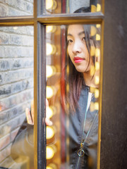 Beautiful Asian girl behind the window. She is standing behind a glass door and looking through glass. Colorful light is reflected in the window on her face.