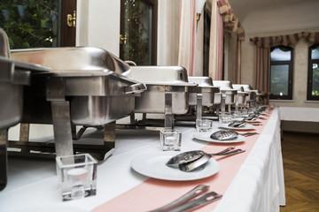 Many white metallic clean modern utensils on wedding buffet