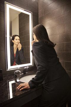 Caucasian businesswoman doing makeup in a mirror.