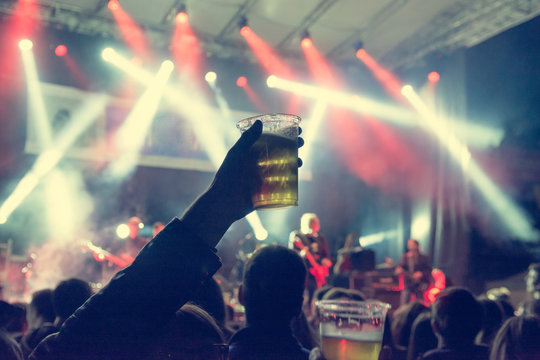 Raised beer glass at a concert.