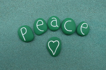 Peace word with green painted sea stones over green sand