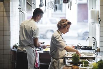 Side view of female chef preparing food on counter in kitchen with male colleague working at restaurant