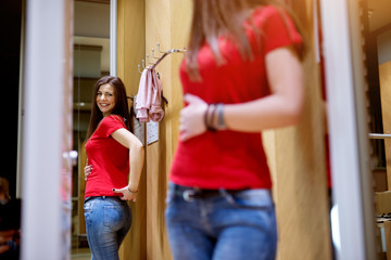 Close up of a young beautiful girl standing in front of a mirror is happy with how her new shirt looks on her.