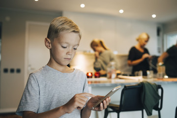 Boy using mobile phone while standing against family in background