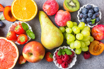 Fresh assorted fruits and berries on light gray background. Colorful clean and healthy eating. Detox food. Top view.