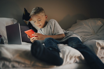 Full length of boy using mobile phone reclining with laptop on bed at home