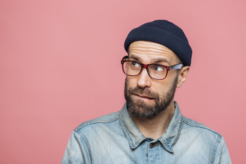 Portrait of unshaven thoughtful middle aged male with pensive expression looks upwards, wears stylish hat, eyewear and denim jacket, isolated over pink background with copy space for your text