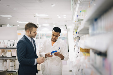 Male pharmacist showing medicine to mature customer standing by rack at medical store