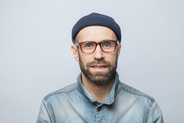 Portrait of handsome stylish male journalist wears eyewear, fashionable hat and denim jacket, poses against white studio background. Satisfied man with stubble has blue eyes and pleasant appearance