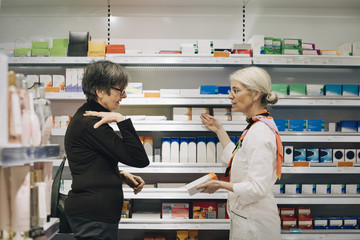 Side view of senior female customer explaining to owner standing by medicine rack at pharmacy store