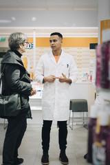Full length of male pharmacist talking with senior female customer in medical store