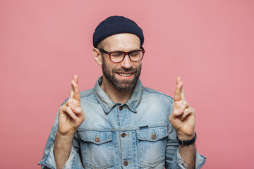Positive unshaven male with glad look crosses fingers, keeps eyes closed, has great desire and hope for better, wears fashionable clothes, isolated over pink background. People and desire concept