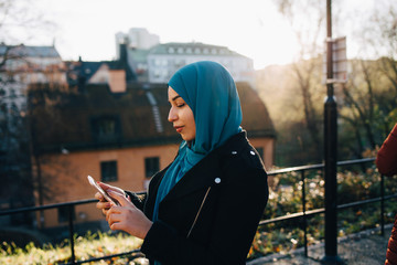 Young Muslim woman wearing hijab using smart phone in city