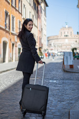 Executive and modern woman walks the street with her luggage and looks back.
