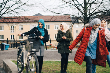 Happy multi-ethnic female friends walking with bicycle on grass in city