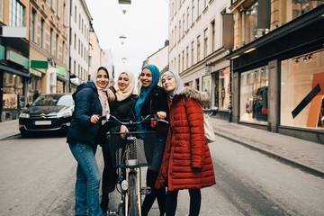 Portrait of smiling multi-ethnic Muslim female friends standing with bicycle on street in city
