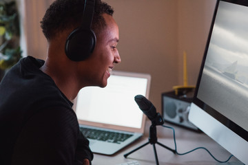 Smiling young freelance worker wearing headphones podcasting in front of computer