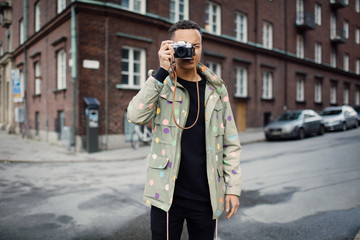 Young photographer taking picture with camera while standing on street