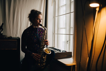 Young woman playing saxophone while practicing by window at studio
