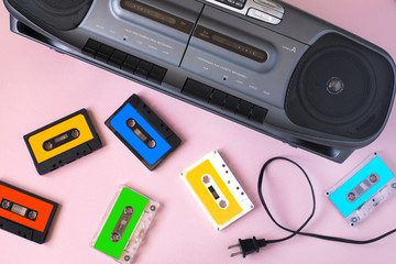 Old black retro cassette music audio tape recorder and retro cassette tape collection on pink background