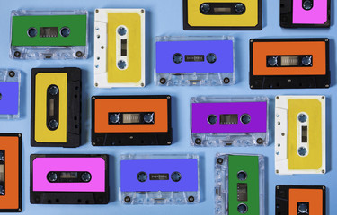 Retro cassette tape collection on blue background, top view.