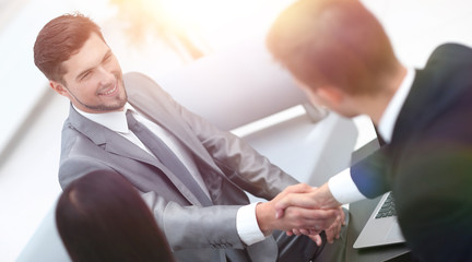 handshake business partners in the lobby of the office.