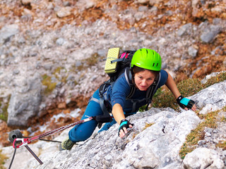 A young brave girl in green helmet going via ferrata in Seeben Klettersteig, Germany