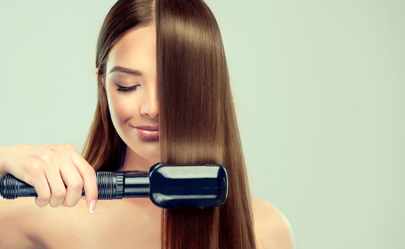 beautiful young woman  using a hair straightener and smiling