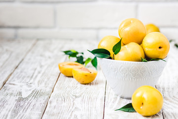 Ripe yellow plums on wooden background. Selective focus, space for text.