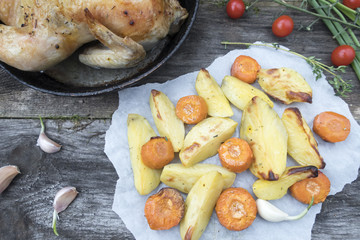Appetizing baked vegetables are potatoes and carrots on an old wooden background and chicken in a frying pan.