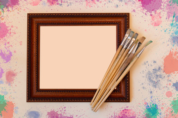 Frame with paint brushes on beige background