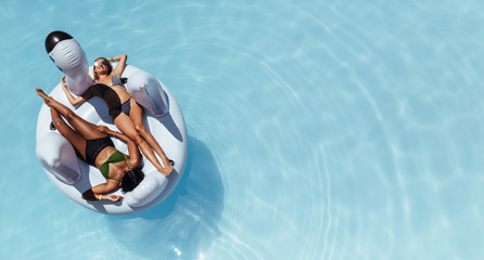 Girls relaxing on floating pool inflatable toy