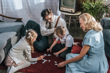 happy family with two children playing dominoes together at home, 1950s
