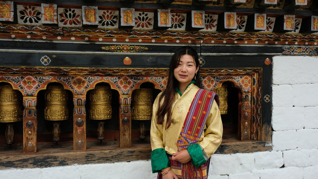 Bhutanese young woman facing the camera with a smile is wearing a kira (national dress) and standing in front of prayer wheels in monastery