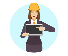 Businesswoman in construction helmet pointing at a digital tablet PC