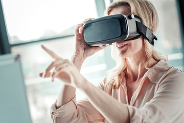 Virtual vision. Cheerful woman keeping smile on her face and stretching hand while looking forward