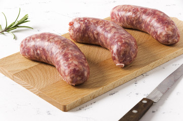Three sausages with rosemary leaves on white background.