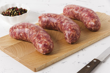 Three sausages on the chopping board on white background and peppercorn