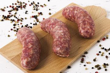 Three raw sausages on cutting board and white background.