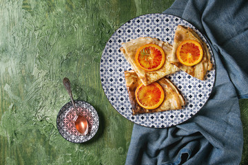 Homemade crepes pancakes served in white decorate ceramic plates with bloody oranges and rosemary syrup with sliced sicilian red oranges over green texture background. Top view, space
