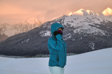 Portrait of woman in snow at sunset