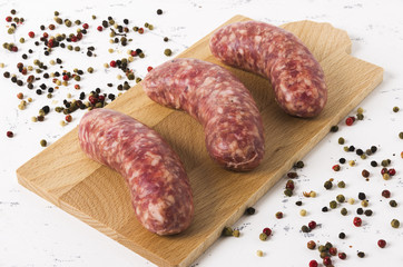 Raw sausages on cutting board and white background.