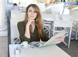 Beautiful young woman reading in the cafe