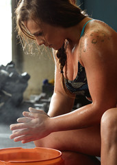 Athletic woman chalking hands during workout
