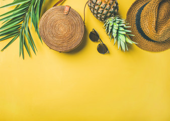 Colorful summer female fashion outfit flat-lay. Straw hat, bamboo bag, sunglasses, palm branches, fresh pineapple over yellow background, top view, copy space. Summer fashion, holiday travel concept Wall mural
