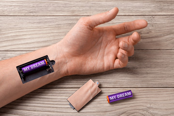 Dream gives strength and energy moves on. Word my dream is written on the battery. Hand of man with a slot for charging batteries.