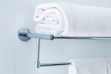 Close up of folded white bathroom towels on the rack in a white bathroom near shower